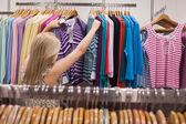 Mujer buscando ropa en el tendedero — Foto de Stock
