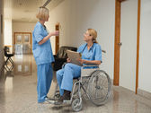 Nurse with drink talking to nurse in wheelchair with folder — Stock Photo