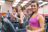 Smiling woman on a treadmill in the gym with — Stock Photo