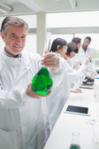 Chemist holding beaker — Stock Photo