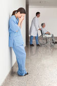 Stressed nurse leaning against wall — Stock Photo