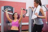 Women using weight machine smiling at friend — Foto de Stock