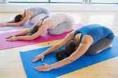 Mujeres haciendo a childs posan en clase de yoga — Foto de Stock