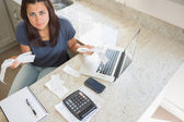 Young woman calculating bills and looking worried — Stock Photo