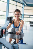 Smiling brunette training on row machine — Stock Photo
