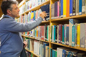 Man taking a book from the shelves — Stock Photo