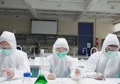 Chemici v ochranných oblecích přidáním tekutiny do petriho misek — Stock fotografie
