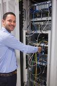 Smiling man adjusting server — Stock Photo