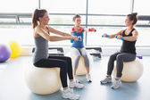 Three women lifting weights together on exercise balls — Stock Photo