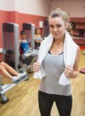 Woman with towel around neck in weights room — Stock Photo