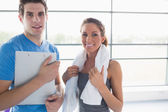 Woman holding a towel and trainer holding a clipboard smiling — Stock Photo