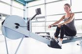 Woman training happily on row machine — Stock Photo