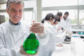 Chemist smiling and holding beaker — Stock Photo