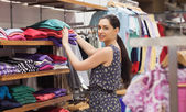 Woman putting jumpers on shelf — Foto Stock