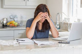 Stressed woman looking down at bills — Stockfoto
