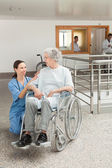 Nurse looking after old women sitting in wheelchair — Stock Photo