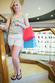 Woman standing on the stairs with shopping bags — Stock Photo