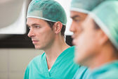 Three surgeons in operating theatre — Stock Photo