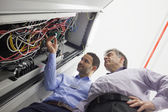 Technicians checking wires of server — Stock Photo