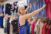 Vrouw op zoek via kleren en glimlachen — Stockfoto
