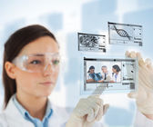 Woman selecting medical images from hologram interface — Stock Photo