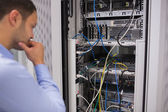 Man looking at rack mounted servers — Stock Photo
