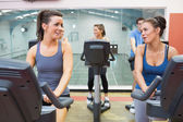 Two women talking while training in a spinning class — Stock Photo