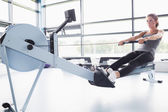 Fit woman training on row machine — 图库照片