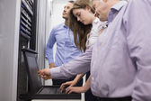 Technicians checking servers with laptop — Stock Photo