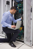 Man fixing wires while doing maintenance in data center — Foto Stock