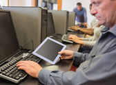 Man in computer class looking at tablet pc — Stock Photo