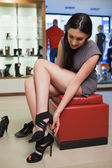 Woman sitting in a boutique trying shoes — Stock Photo