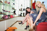 Women trying on shoes smiling — Stock Photo