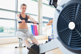 Woman exercising on row machine — Stock Photo