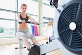 Woman exercising on row machine — Stock Photo
