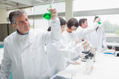 Chemists doing research on green liquid — Stock Photo