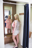 Woman looking in the mirror — Stockfoto