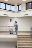 Nurse and doctor having a discussion at top of stairwell — Stock Photo