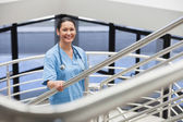 Smiling nurse in a stairwell — Stock Photo