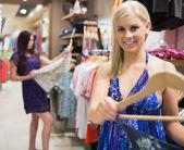 Vrouw met jurk op de hanger en glimlachen — Stockfoto