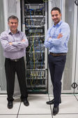Two technicians standing in front of servers — Stock Photo