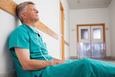 Tired surgeon is sitting on the floor in hospital corridor — Stock Photo