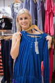 Woman holding up blue shirt — Stock Photo