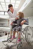Doctor talking to child with neckb race in wheelchair — Stock Photo