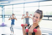 Smiling woman lifting weights while women doing aerobics — Stok fotoğraf