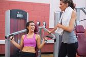 Woman using weights machine talking to friend — Stock Photo