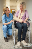 Nurse talking with patient in wheelchair with arm in sling — Stock Photo