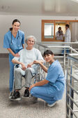 Two nurses with old woman in wheelchair — Stock Photo