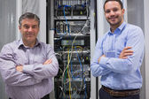 Technicians smiling while standing in front of servers — ストック写真
