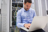 Man using laptop to check servers — Stockfoto